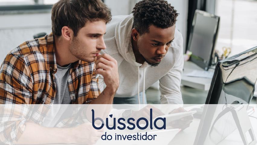 Homem branco e negro olhando a tela de um computador.