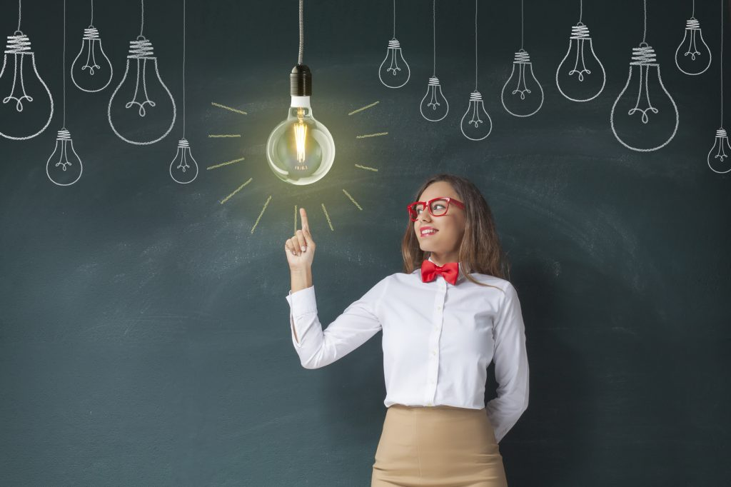 Young teacher pointing light bulb on blackboard background