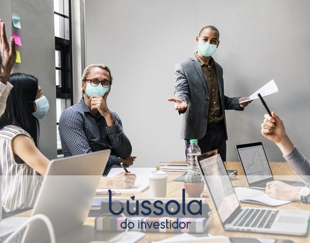 Pessoas em uma mesa discutindo se vale a pena investir durante a pandemia