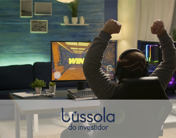 Homem em frente ao computador torcendo em uma partida do mercado gamer